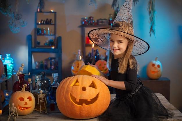 Красивая маленькая девочка в костюме ведьмы на хэллоуин Premium Фотографии
