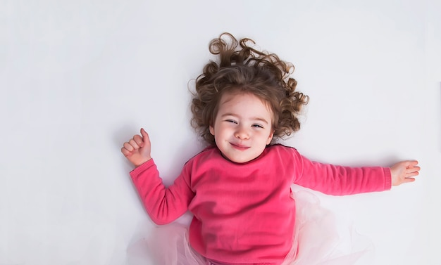 Beautiful little girl lies on the white floor and smile. the concept of a happy childhood. Premium Photo