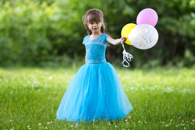 Beautiful little girl in nice long blue evening dress looking like princess looks  holding colorful balloons Premium Photo