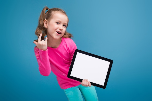 Beautiful little girl in pink shirt with monkey and blue trousers hold empty tablet Premium Photo