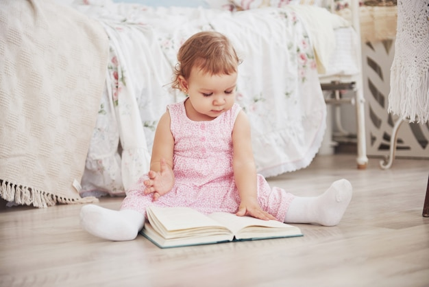 Beautiful little girl playing toys. blue-eyed blonde. white chair. children's room. happy small girl portrait. childhood concept Premium Photo