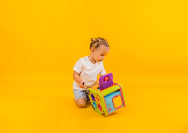 Beautiful little girl playing with a large educational toy on a yellow background with space for te