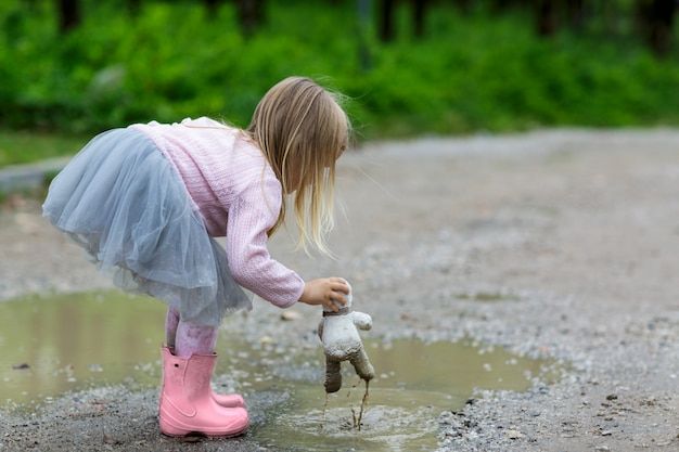 Beautiful little girl in a tutu skirt batting a teddy bear in a puddle on the street Premium Photo