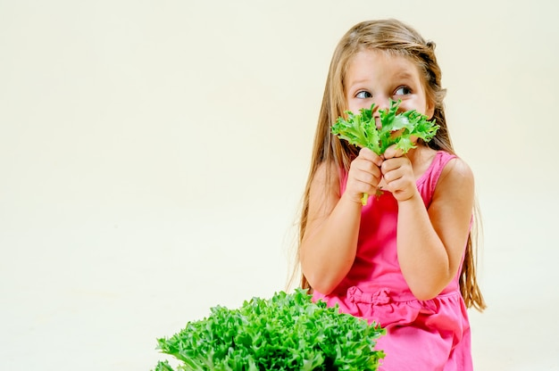 Beautiful little girl with lettuce in hand on a light monophonic background, proper nutrition Premium Photo