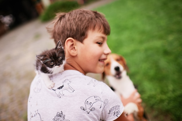 Beautiful little kitty sits on boy's shoulder Free Photo