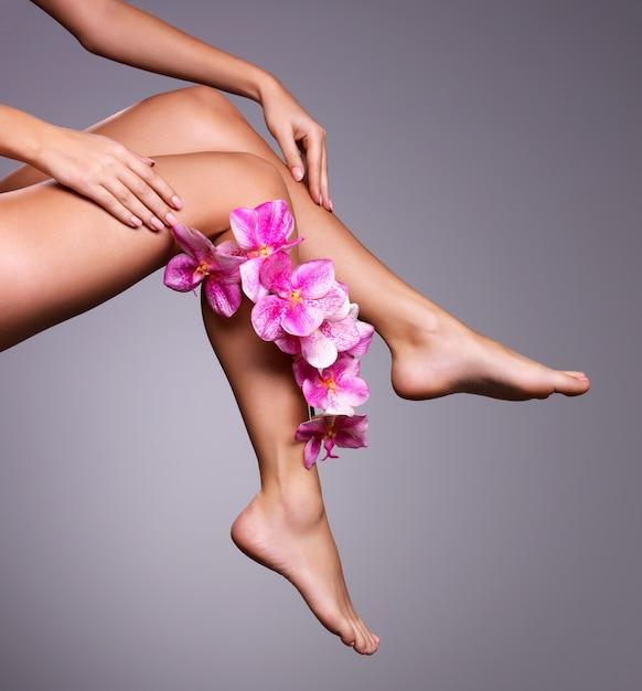 Красивые длинные женские ножки с цветком. концепция лечения красоты Бесплатные Фотографии
