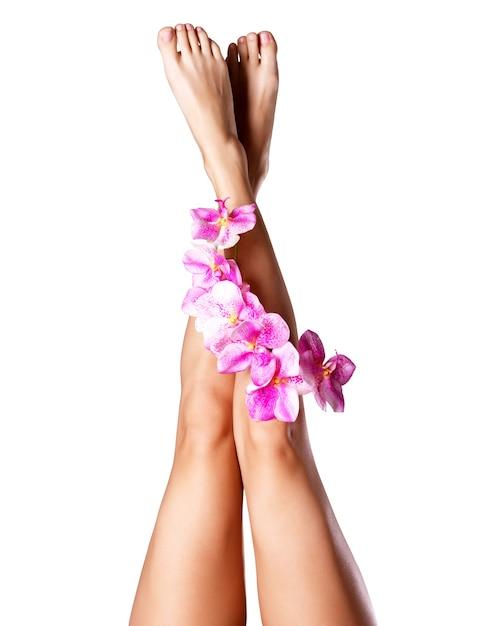 Bei piedini femminili lunghi con il fiore. concetto di trattamento di bellezza Foto Gratuite