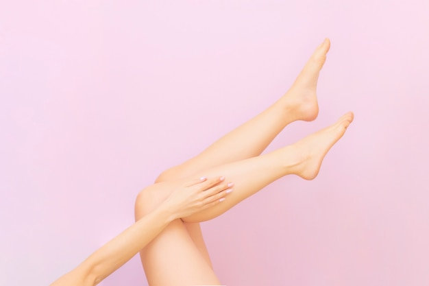 Beautiful long female legs with smooth skin after depilation on pastel pink Premium Photo
