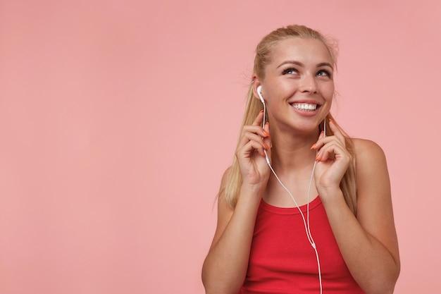 Красивая длинноволосая блондинка с наушниками слушает любимую музыку, весело улыбается и смотрит вверх Бесплатные Фотографии