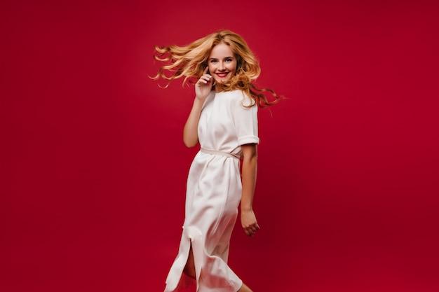 Красивая длинноволосая девушка танцует с улыбкой на красной стене. блаженная кавказская дама в белом платье веселится на вечеринке. Бесплатные Фотографии
