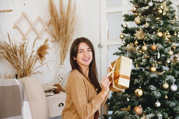 선물 황금 상자를 들고 카메라에 미소 크리스마스 트리 근처 아름다운 장발 소녀 프리미엄 사진