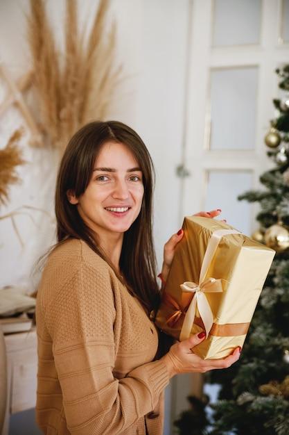황금 선물을 들고 카메라에 미소 크리스마스 트리 근처 아름다운 장발 소녀 프리미엄 사진