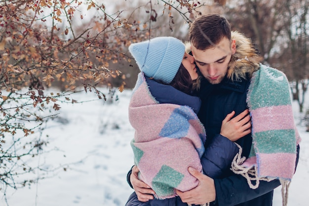 Beautiful loving couple walking and hugging in winter forest. people warming covered with blanket Premium Photo