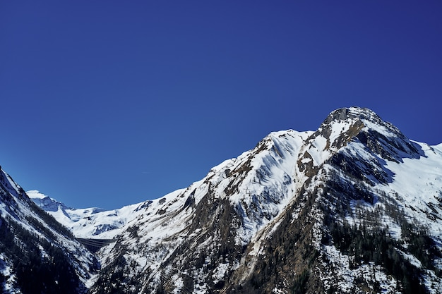 Beautiful low angle shot of a mountain with snow covering the peak and the sky in the background Free Photo