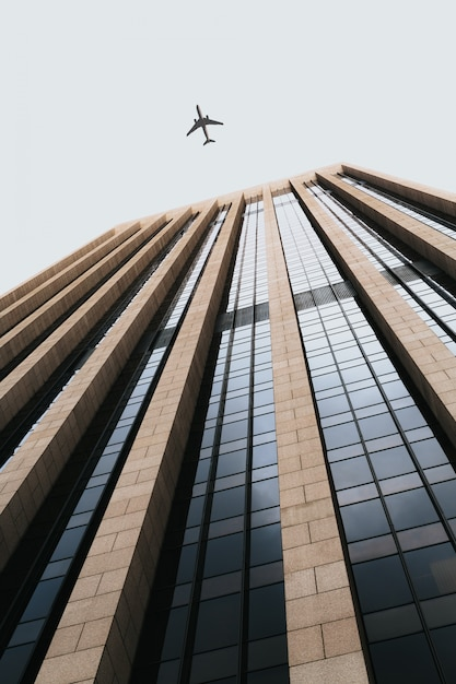 Beautiful low angle shot of a tall business building with an airplane flying overhead Free Photo
