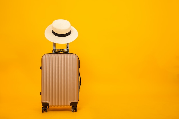 Beautiful luggage and hat isolated on yellow background, accessory travel concept. Premium Photo