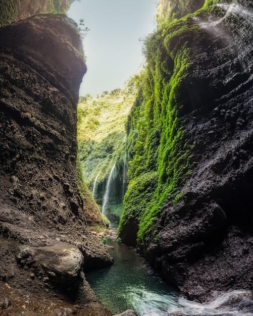 Beautiful madakaripura waterfall in rocky valley Premium Photo