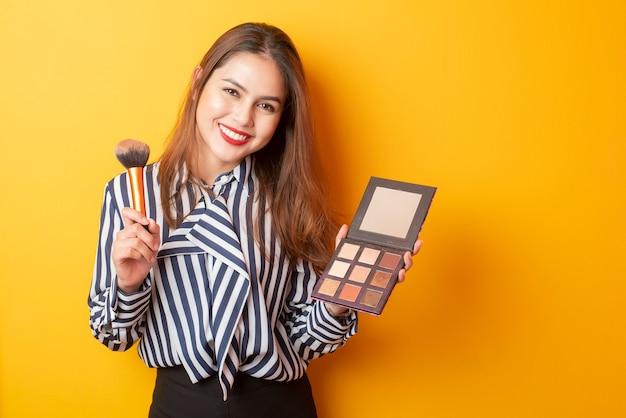 Beautiful makeup artist woman is happy on yellow background Premium Photo