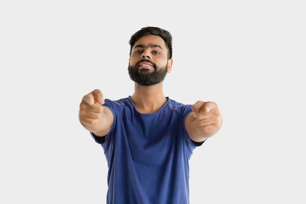 Bellissimo ritratto maschile isolato. giovane uomo indù emotivo in camicia blu. espressione facciale, emozioni umane. indicare e scegliere. Foto Gratuite