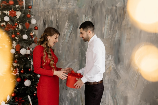 Beautiful man and woman in fancy closes pose before rich decorated christmas tree and exchange their Free Photo