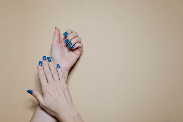 Beautiful manicured woman's nails with classic blue nail polish on beige Premium Photo
