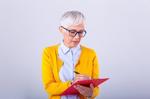 Beautiful mature businesswoman writing in clipboard isolated on white. portrait senior business women with clipboard and document in hands Premium Photo