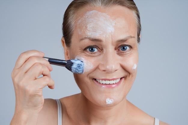 美しい成熟した女性は、ブラシで彼女の顔に化粧マスクを適用します。高齢者のスキンケアに直面します。 Premium写真