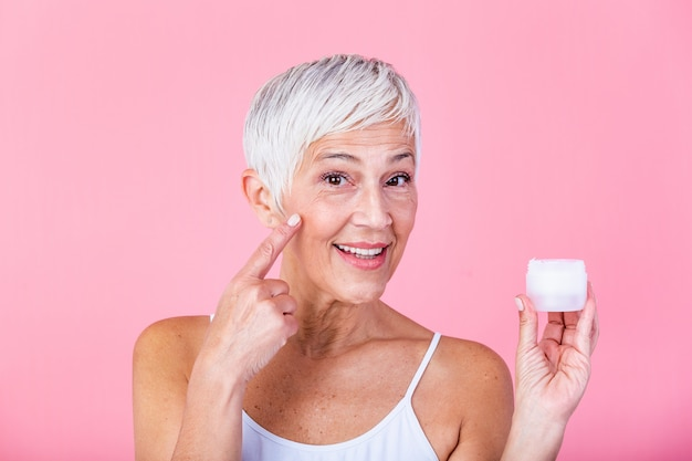 Beautiful mature woman holding jar of moisturizer and looking at camera. happy senior woman holding a bottle of anti-aging lotion isolated over pink background. anti aging and beauty treatment. Premium Photo