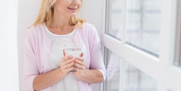 Beautiful mature woman posing with a glass of water Free Photo