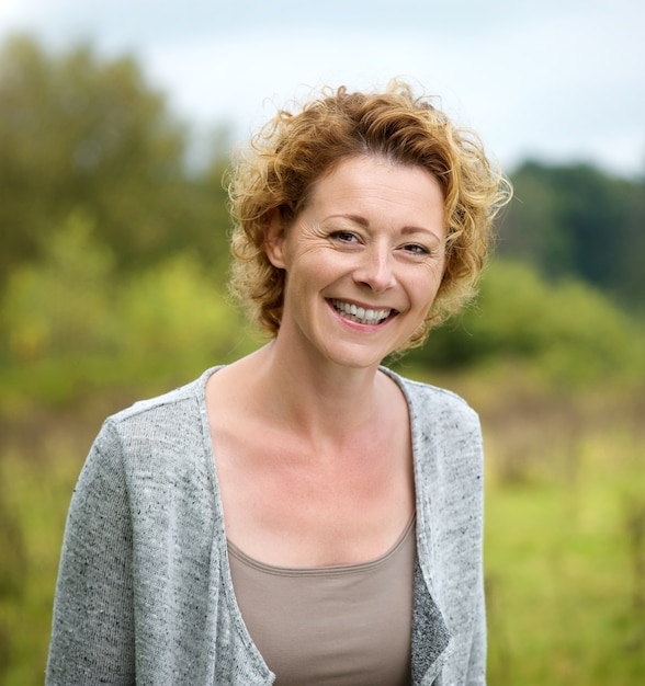 Head shot close up portrait of pleasant smiling mature woman happy healthy middle aged lady relaxing alone