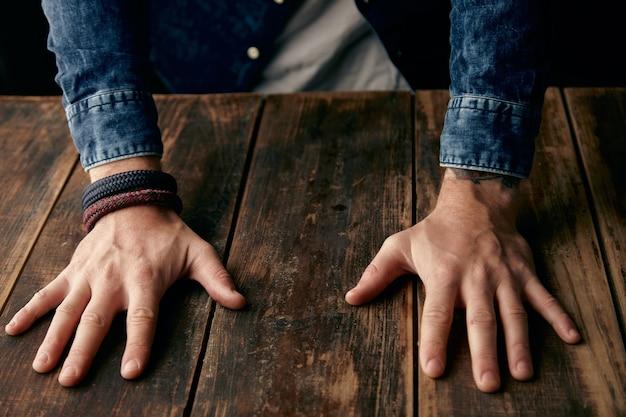 Belle mani di uomini sul tavolo, camicia casual di jeans, tatuaggio, cinturino da polso, braccialetti Foto Gratuite
