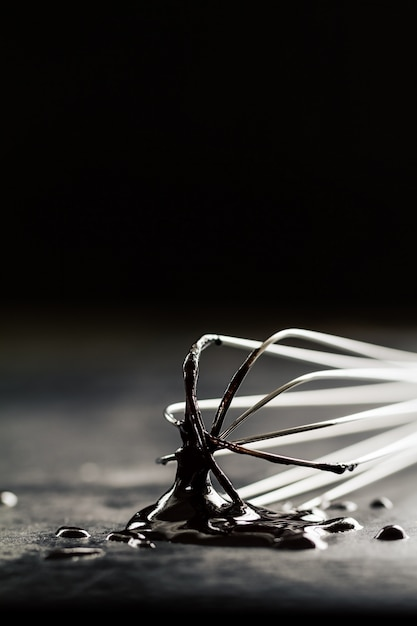 Beautiful Metal Baker Whisk With Chocolate On Dark Table