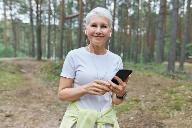 Bella donna caucasica di mezza età con i capelli corti godendo la mattina d'estate all'aperto, andando ad avere un allenamento cardio, scegliendo brani musicali sul cellulare Foto Gratuite