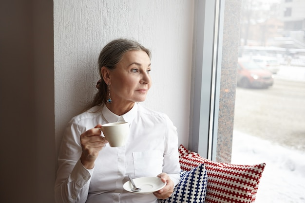 窓辺の食堂に座って、朝のコーヒーを楽しんだり、カップを持って窓越しに見たり、白髪と青い目をした美しい中年女性、心のこもった表情 無料写真