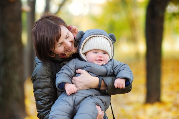 Beautiful middle aged woman and her adorable little grandson in the autumn park Premium Photo