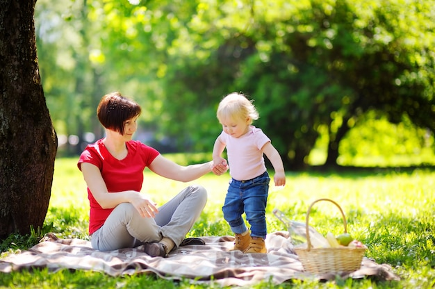 Beautiful middle aged woman and her adorable little grandson having a picnic in sunny park Premium Photo