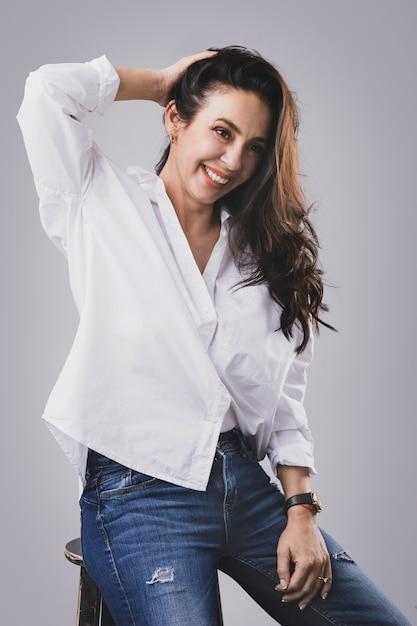 白いシャツとジーンズを着て美しい中年女性 Premium写真
