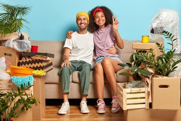 美しい混血カップルがソファに寄り添い、満足し、新しい家に移動することを喜ぶ 無料写真