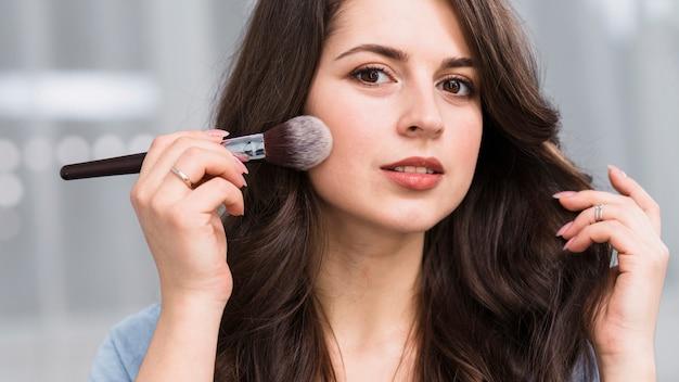 Beautiful model posing with powder brush Free Photo