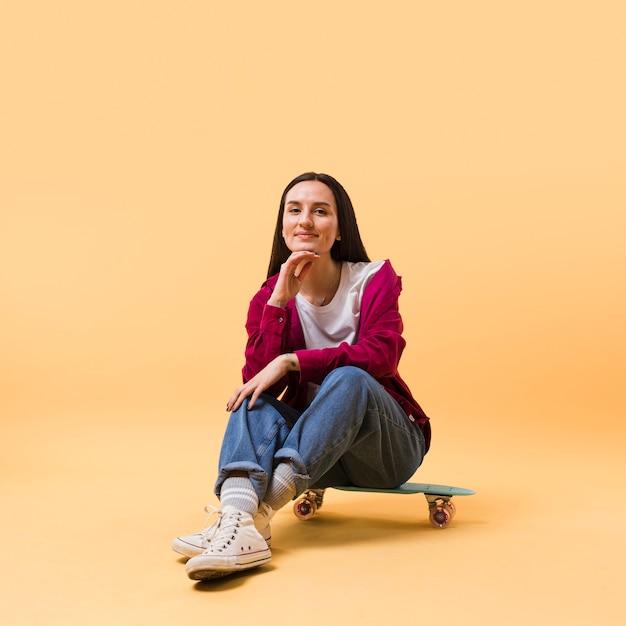 Красивая модель сидит на скейтборде Premium Фотографии
