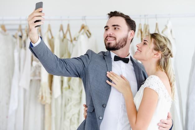 Beautiful model wedding couple holding smart phone online