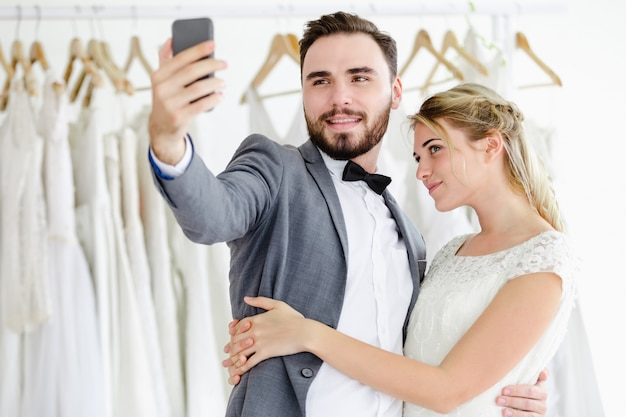 Beautiful model wedding couple holding smartphone online video call looking at screen Premium Photo