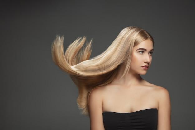 ダークグレーのスタジオの背景に分離された長く滑らかな、飛んでいるブロンドの髪を持つ美しいモデル。手入れの行き届いた肌と髪が空気を吹いている若い白人モデル。 無料写真