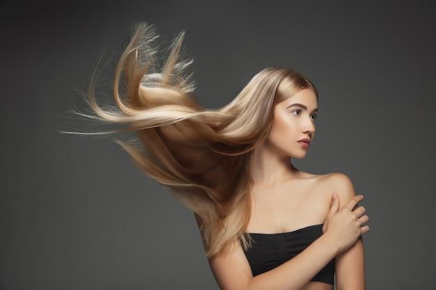 어두운 회색 스튜디오 배경에 고립 된 긴 부드럽고 비행 금발 머리를 가진 아름 다운 모델. 잘 관리 된 피부와 머리가 공기에 날리는 젊은 백인 모델. 무료 사진