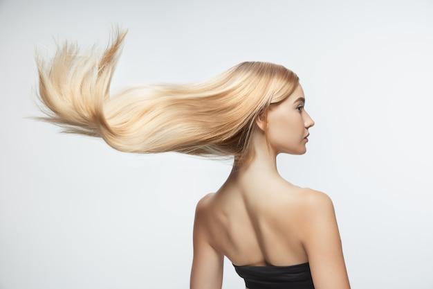 白いスタジオの背景に分離された長く滑らかな、飛んでいるブロンドの髪を持つ美しいモデル。手入れの行き届いた肌と髪が空気を吹いている若い白人モデル。 無料写真
