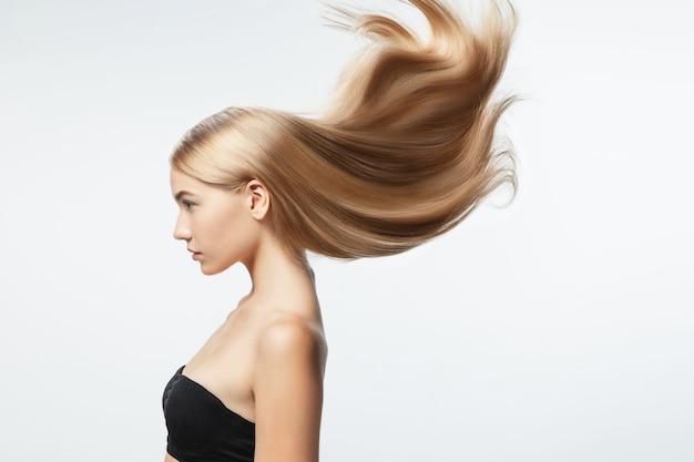 흰색 스튜디오 배경에 고립 된 긴 부드럽고 비행 금발 머리를 가진 아름 다운 모델. 잘 관리 된 피부와 머리가 공기에 날리는 젊은 백인 모델. 무료 사진