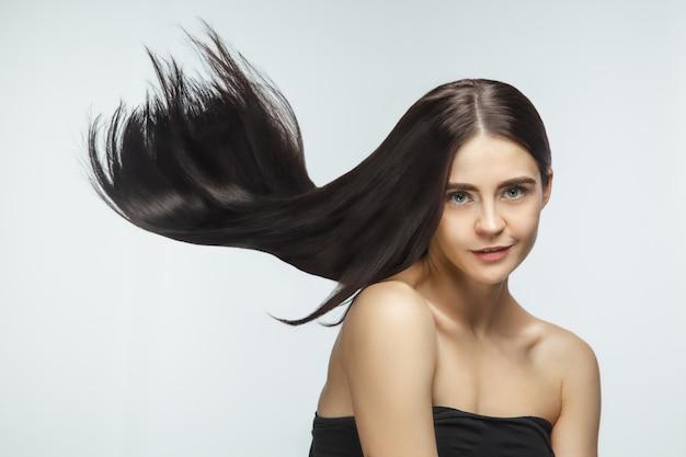 白いスタジオの背景に分離された長く滑らかな、飛んでいるブルネットの髪を持つ美しいモデル。 無料写真