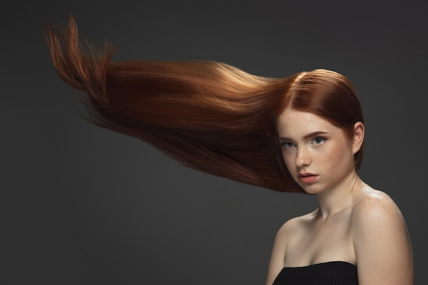 Beautiful model with long smooth, flying red hair isolated on dark Free Photo