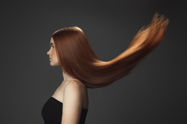 Красивая модель с длинными гладкими, развевающимися рыжими волосами, изолированными на темноте Бесплатные Фотографии