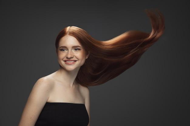 暗闇で隔離の長く滑らかな、飛んでいる赤い髪の美しいモデル 無料写真